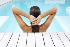 Mujer en piscina en el Poolside que tira del pelo Foto de archivo libre de regalías