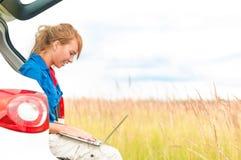 Mujer en prado cerca del coche que trabaja en la computadora portátil. Fotografía de archivo