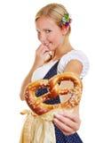Mujer en pretzel de ofrecimiento del dirndl Foto de archivo