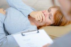 Mujer en rasgones que habla con el terapeuta foto de archivo libre de regalías