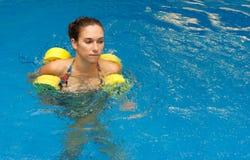 Mujer en retén del agua con pesas de gimnasia Imagen de archivo