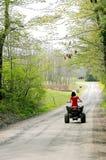 Mujer en rojo en el coche de cuatro ruedas Foto de archivo