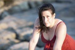 Mujer en rojo en la playa rocosa en la puesta del sol 5 Imágenes de archivo libres de regalías