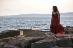 Mujer en rojo en la playa rocosa en la puesta del sol 3 Fotos de archivo libres de regalías