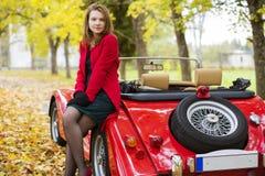 Mujer en rojo y coche en el parque Imágenes de archivo libres de regalías