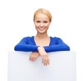 Mujer en ropa casual con el tablero blanco en blanco Fotos de archivo