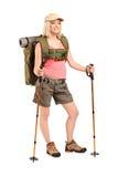 Mujer en ropa de deportes con el morral y los postes el ir de excursión foto de archivo