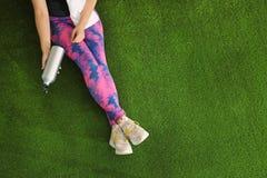 Mujer en ropa de deportes con la botella de agua y de toalla que se sientan en la hierba artificial, visión superior fotos de archivo