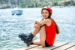 Mujer en ropa de deportes con los rodillos patinadores en Foto de archivo libre de regalías