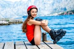 Mujer en ropa de deportes con los rodillos patinadores en Imágenes de archivo libres de regalías