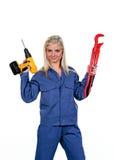 Mujer en ropa de trabajo azul con el taladro Imagenes de archivo
