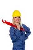 Mujer en ropa de trabajo azul con la llave de tubo Imagen de archivo