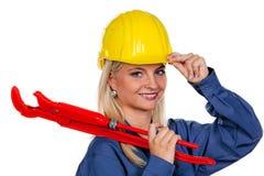 Mujer en ropa de trabajo azul con la llave de tubo Fotografía de archivo