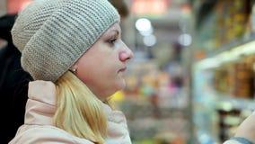 Mujer en ropa del invierno en un supermercado que lee los textos en un tarro de comida Ella pone el tarro en el estante del almacen de metraje de vídeo