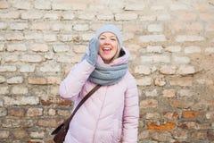 Mujer en ropa informal que llama el grito en espacio de la copia de la pared de ladrillo foto de archivo libre de regalías