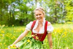 Mujer en ropa o dirndl bávara en un prado Foto de archivo libre de regalías