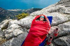 Mujer en saco de dormir en la montaña Fotografía de archivo