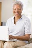 Mujer en sala de estar con la sonrisa de la computadora portátil imagen de archivo