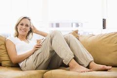 Mujer en sala de estar que escucha el jugador MP3 Fotos de archivo libres de regalías