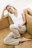 Mujer en sala de estar que escucha el jugador MP3 Imagenes de archivo