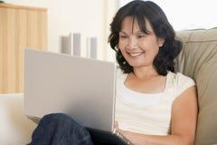 Mujer en sala de estar usando la computadora portátil Imagenes de archivo