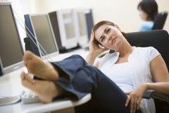 Mujer en sala de ordenadores con los pies para arriba que piensa Imagen de archivo