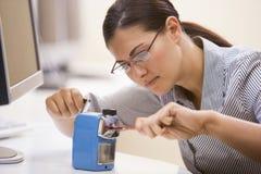 Mujer en sala de ordenadores usando los sacapuntas de lápiz Imagenes de archivo