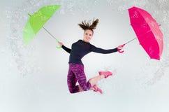 Mujer en salto con un paraguas foto de archivo