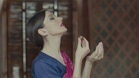 Mujer en sari que huele el aroma delicioso de la bolsita almacen de video