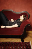 Mujer en serie rojo del sofá Foto de archivo libre de regalías