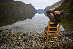 Mujer en silla cerca de orillas del lago Fotos de archivo libres de regalías