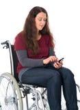 Mujer en silla de ruedas con el teléfono Imágenes de archivo libres de regalías