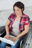 Mujer en silla de ruedas que mecanografía en el ordenador portátil Imagen de archivo