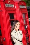 Mujer en smartphone por la cabina de teléfono roja de Londres Imagenes de archivo