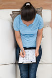 Mujer en Sofa Filling Survey Form Imagen de archivo