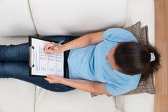 Mujer en Sofa Filling Survey Form Fotografía de archivo libre de regalías