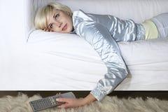 Mujer en Sofa With Remote Control Imagenes de archivo