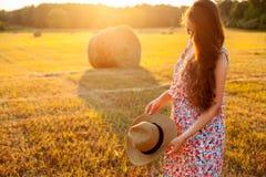 Mujer en sombrero con el pelo rizado que se coloca en el campo Fotografía de archivo libre de regalías