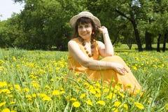 Mujer en sombrero con los dientes de león amarillos Imagenes de archivo