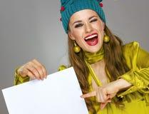 Mujer en sombrero de la Navidad que guiña y que señala en el papel en blanco Fotos de archivo
