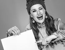 Mujer en sombrero de la Navidad que guiña y que señala en el papel en blanco Fotografía de archivo libre de regalías