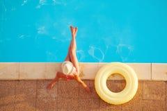 Mujer en sombrero de paja con el anillo de goma por la piscina imagenes de archivo