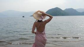 Mujer en sombrero de seda rosado del vestido y de paja que camina en la playa almacen de metraje de vídeo