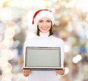 Mujer en sombrero del ayudante de santa con el ordenador portátil Fotos de archivo