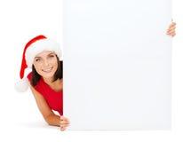 Mujer en sombrero del ayudante de santa con el tablero blanco en blanco Imagenes de archivo