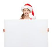 Mujer en sombrero del ayudante de santa con el tablero blanco en blanco Imagen de archivo libre de regalías