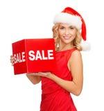 Mujer en sombrero del ayudante de santa con la muestra roja de la venta Fotografía de archivo libre de regalías