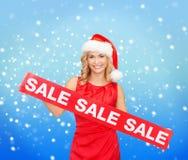 Mujer en sombrero del ayudante de santa con la muestra roja de la venta Foto de archivo