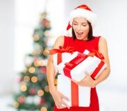 Mujer en sombrero del ayudante de santa con muchas cajas de regalo Fotos de archivo libres de regalías