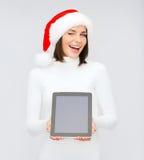 Mujer en sombrero del ayudante de santa con PC de la tableta Imagen de archivo
